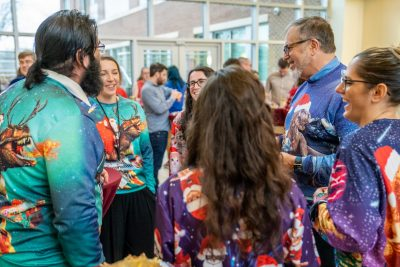 Graduate students and PIs mingle at our annual holiday party, featuring  lively outfits, and musical and creative performances by our faculty, staff, and students.