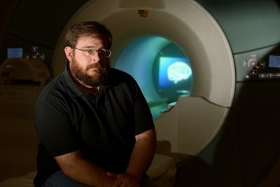Stephen LaConte sits in front of an MRI scanner