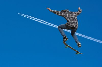 A teenager skateboards with the contrails of a jet in the background